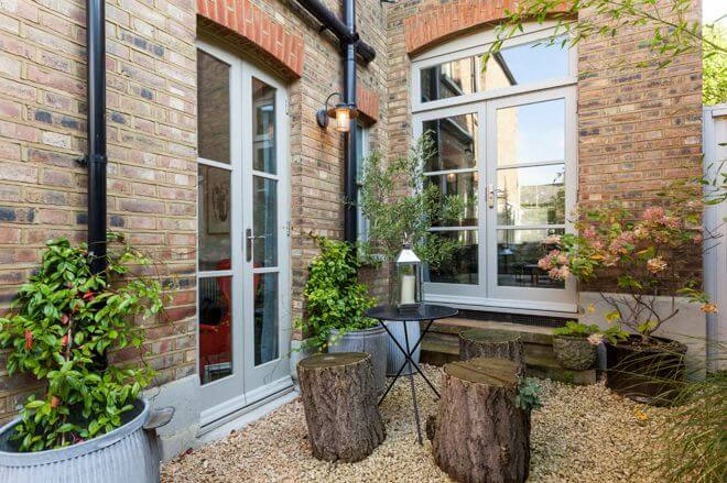 By using log seats, lots of plants and a lovely pea gravel, this small patio blends in well with the landscape and the home. The space is a rustic little secret garden.