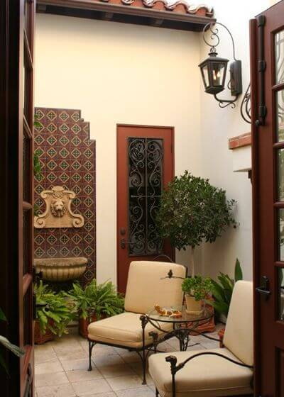 On a patio without much space on the ground, use walls to mount elements like fountains, sculptures, window boxes and lighting.
