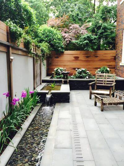 You'd be surprised how well a small patio can take on water features. This urban garden in Washington, D.C., has a wonderfully scaled, stepped-down narrow trough fountain that hugs the perimeter of the patio and helps to mitigate the city noise.