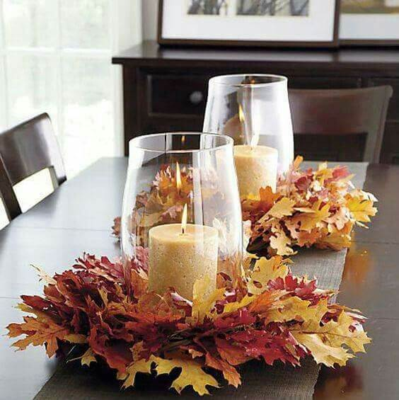 Wreath of colorful leaves provide the base for a pillar candle | DIY Fall Candle Decoration Ideas - Farmfoodfamily.com