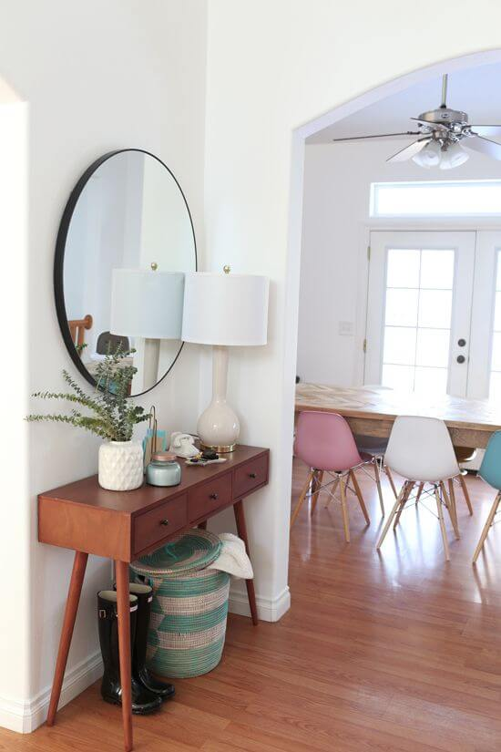 A big round mirror above table with a skinny lamp | Best Small Entryway Decor & Design Ideas | Small Mudroom Ideas | FarmFoodFamily.com